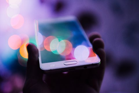 Blog header image for See How Acumatica Mobile Apps Keep You Connected from Anywhere depicting image of mobile phone with colorful lights for act-connect blog